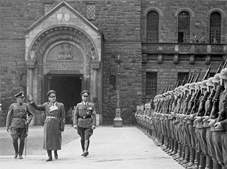 Arthur Greiser - Reviewing the troops in Poznań, November 1939.  Greiser is on the right with Wilhelm Frick (center) and Generalmajor Walter Petzel (left).