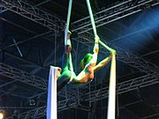 A performer hangs, back arched, between two sheets of tensile fabric.