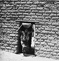 COLLECTIE TROPENMUSEUM Een Samo vrouw met schaal op haar hoofd passeert een deuropening TMnr 20010249.jpg