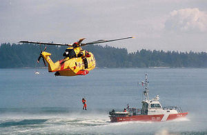 Search and rescue - A Canadian Forces CH-149 Cormorant helicopter hoists a man from a Canadian Coast Guard cutter