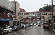 Tourist shops and historical remnants of the sardine canning industry line both sides of Cannery Row, which is busy even though it is raining. Two bridges that are labeled with the company names of defunct sardine canneries stretch over the street, connecting buildings on either side.