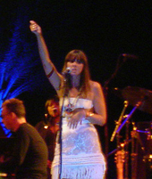 A female vocalist wearing a white dress performing on stage. Some members of a string section present in the left-hand side and part of a drum kit present on the right