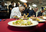 Certified Executive Chef Joseph Rodrigues, left at table, and U.S. Navy Cmdr. Michael Harris, center at table, the commanding officer of the amphibious dock landing ship USS Pearl Harbor (LSD 52), judge food 130623-N-SK590-272.jpg