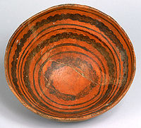 A color picture of an orange ceramic bowl