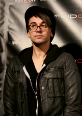 A man wearing glasses and a black shirt and jacket