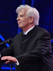 elderly man with full head of white hair in formal attire