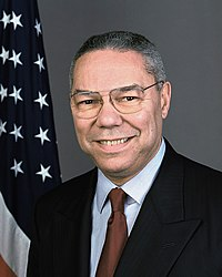 Colin Powell smiling with eye glasses wearing a dark suit jacket, white button-shirt with collar, and a solid burgundy tie.  The United States flag is in the background.