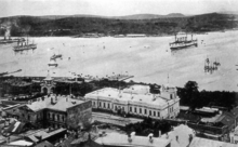 Photograph of ships in a bay, with buildings in the foreground