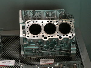 Cylinder block - A V6 diesel engine block, with both of the cylinder banks as well as the crankcase formed en bloc. The large holes are the cylinders, while the small ones are the mounting holes (round) and coolant or oil ducts (oval).