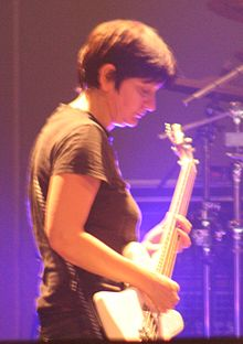 A woman performing onstage with a white bass guitar. She is illuminated by blue lighting.