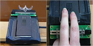 Saccadic suppression of image displacement - Apparatus. Refreshable Braille cells are embedded in an inclined surface (left). A sliding potentiometer supports two semicylindrical cradles forming a guide that can be relocated on a Velcro surface to accommodate the participants' anatomical differences.