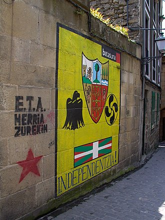 "ETA (separatist group) - Graffiti in Pasaia (2003). ""ETA, the people with you"" on the left, and Batasuna using several nationalist symbols asking for ""Independence!"""
