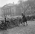 Een studente moet andere fietsen opzij zetten, op de binnenplaats van het Trinit, Bestanddeelnr 191-0860.jpg