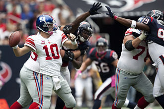 New York Giants - Eli Manning lines up a pass just out of the reach of Houston Texans defenders in 2010.