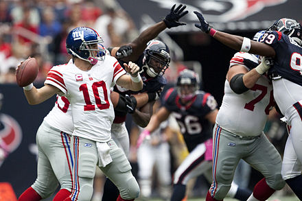 Eli Manning lines up a pass just out of the reach of Houston Texans defenders in 2010. Eli Manning vs Texans October 2010.jpg