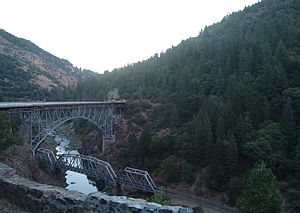 A river flowing between two wooded mountains with a railroad trestle crossing it and a higher road bridge past the trestle