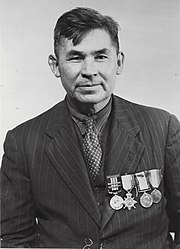 older man with suit, tie, and medals on his chest