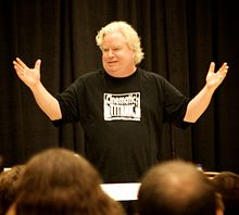 Photo of a man in giving a presentation to an audience in front of a theatrical curtain
