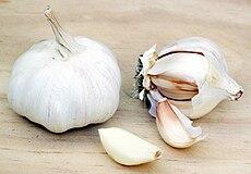 Garlic bulbs and individual cloves, one peeled.