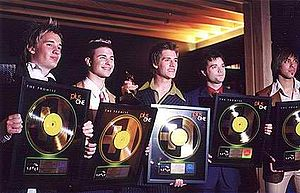 Music recording sales certification - Boy band Plus One displaying their gold records
