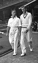 Two men in cricket uniforms walk along a paved path, wearing white shirts, trousers and shoes. The man on the left has his sleeves rolled up, while his taller colleague is wearing a woolly sweater. Both have dark hair. Manicured grass is to their left and a pavilion is behind them.