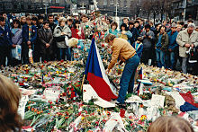 Un homme de profil au milieu d'une foule en recueillement, aux côtés d'un drapeau tchécoslovaque, le sol est tapissé de roses.