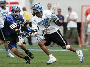 Field lacrosse - Kyle Harrison advancing, pursued by an opponent