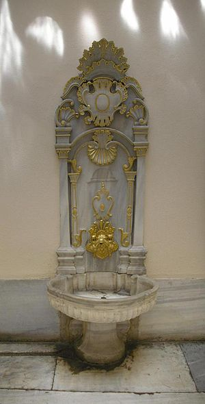 One of the gilded taps with marble in the bath...