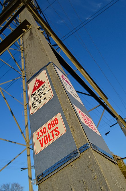 Power lines with high voltage warning sign. HydroOnePowerTower2.jpg