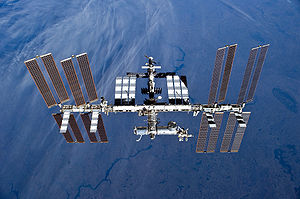 A planform view of the ISS backdropped by the limb of the Earth. In view are the station's four large, gold-coloured solar array wings, two on either side of the station, mounted to a central truss structure. Further along the truss are six large, white radiators, three next to each pair of arrays. In between the solar arrays and radiators is a cluster of pressurised modules arranged in an elongated T shape, also attached to the truss. A set of blue solar arrays are mounted to the module at the aft end of the cluster.
