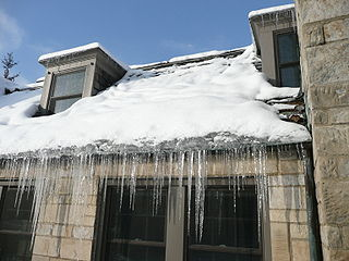 Ice dam (roof) ice build-up on the eaves of sloped roofs of heated buildings