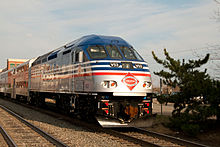 Blue and silver train engine with red and white accent lines moves closer leading a series of similarly colored passenger cars with shrubs and a sound wall in the background.