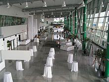 Airport terminal, with small round tables covered with large white tablecloths