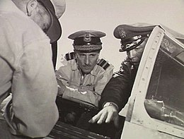 Three men in military uniforms with peaked caps crowding around the open cockpit of a military aircraft, two facing the camera and one with his back turned. The central figure in the portrait, facing the camera, has two rows of braid on the visor of his cap, and pilot's wings on the left breast pocket.
