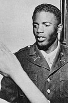 Black man in military uniform featuring the crossed-sabre insignia of a U.S. Cavalry unit receives a salute from a person out of view.