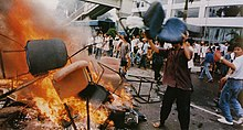 A man wearing a buttoned shirt, pants, and flip-flops throws an office chair into a burning pile of other chairs in the middle of a city street. Behind him, several dozen people gather in front of a building with broken windows.