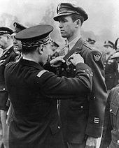 A military officer pinning an award to Stewart's decorated military jacket among other uniformed soldiers