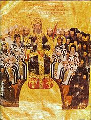 Homme âgé assis en robes noires et dorées, portant une couronne dorée et tenant un sceptre au centre.  Derrière et autour de lui, disposés en demi-cercle, sont assis des hommes barbus, certains en blanc et d'autres en robe noire.  Des têtes barbus d'autres hommes avec des chapeaux tubulaires et triangulaires sont visibles derrière eux.