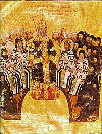 Sitting elderly man in black and gold robes, wearing a golden crown and holding scepter in the center. Behind and around him, arranged in a semicircle, are seated bearded men, some in white and others in black dress. Bearded heads of other men with tubular and triangular hats are visible behind them.