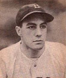 "A man in a white baseball jersey and a dark cap with a white ""B"" on the center looks to the right."