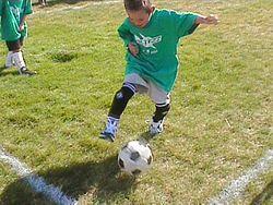 Um menino jogando futebol.