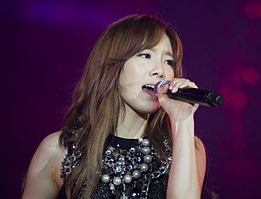Kim Tae-yeon is performing onstage with a mic in her left hand