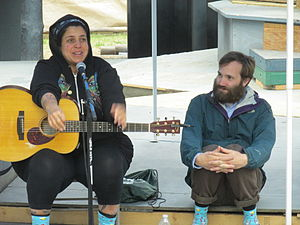 "Kimya Dawson - Kimya Dawson with Paul Baribeau in June 2014.  The two are wearing matching socks with a design similar to many of Dawson's album covers, with the words ""Kimya Dawson Loves Me"" appearing amongst cartoon rabbits."