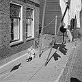 Kind op een fietsje op straat waar de was hangt op de achtergrond een kinderbox, Bestanddeelnr 254-3988.jpg