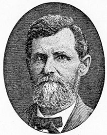 A middle-aged man with a graying beard is wearing a bow tie and suit jacket