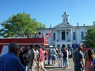 Oxford, Mississippi - A British double-decker tourist bus and the Mississippi state flag contrast beside the Lafayette County Courthouse in Oxford, Mississippi, during the 2007 Double Decker Festival.