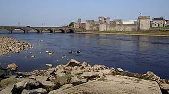 History of Limerick - King John's Castle, built in the 13th century, lies alongside the River Shannon. Thomond Bridge (on the left of this photograph), from the 19th century, stands on the site of an earlier bridge.