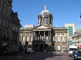 A neoclassical building in two storeys with a central portico and a dome seen almost end-on.  It is flanked on each side by other buildings
