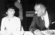 A middle-aged lady wearing a light-coloured dress and with short hair, fluffy at the front, sits at a dinner table smiling. To the right is a taller, older man in a dark suit, striped tie and light shirt who is turning his head to the left, talking to her. A man in a suit is visible, standing in the background.