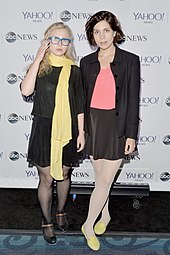 Members Alyokhina and Tolokonnikova at a press event. They are wearing black dress clothes accented by color.
